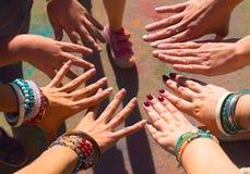 Друзья кладя их руки совместно в знак единства и команды стоковое фото rf