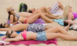 Друзья кладя на песок на пляже Стоковое Изображение