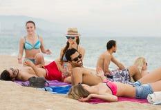 Друзья кладя на песок на пляже Стоковое фото RF