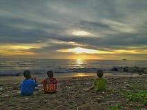 Друзья, море, заход солнца, и погань Стоковое Фото