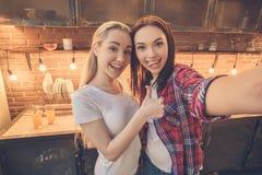 Друзья молодых женщин варя еду совместно дома Стоковые Изображения RF