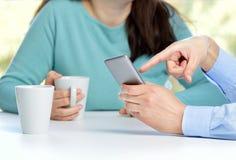друзья наблюдая средства массовой информации в умном телефоне стоковое фото rf