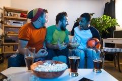 Друзья наблюдая футбольную игру Стоковое фото RF