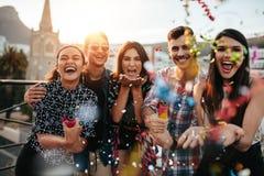 Друзья наслаждаясь партией и бросая confetti Стоковая Фотография