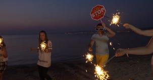 Друзья наслаждаясь партией ночи на побережье акции видеоматериалы