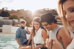 Друзья наслаждаясь пить во время партии крыши Стоковые Фотографии RF