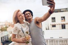 Друзья наслаждаясь пить во время партии крыши Стоковые Изображения
