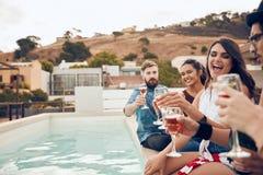 Друзья наслаждаясь пить во время партии крыши Стоковые Изображения RF