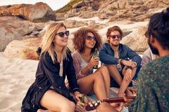 Друзья наслаждаясь пляжем party с музыкой и пить Стоковое Изображение RF