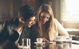 Друзья на кафе используя мобильный телефон Стоковые Изображения