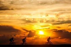 Друзья на отключении велосипеда на заходе солнца Активный образ жизни, задействуя хобби Стоковое Фото