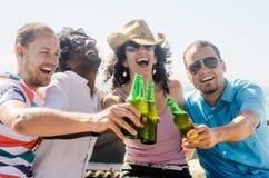 Друзья на партии пляжа имея пить стоковые фото