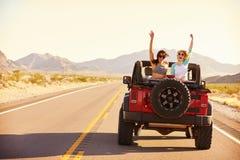 Друзья на поездке управляя в обратимом автомобиле стоковое изображение rf