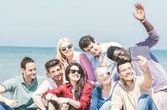 Друзья на пляже смотря таблетку стоковые изображения rf