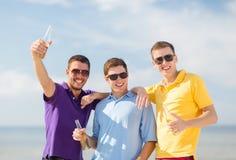 Друзья на пляже с бутылками питья Стоковые Изображения RF