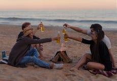 Друзья на пляже party выпивая спирт и clink стекла стоковое изображение rf