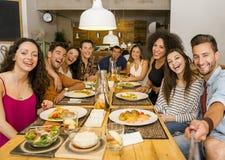 Друзья на ресторане делая selfie стоковая фотография rf