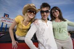 Друзья нося солнечные очки с автомобилем и шильдиком на заднем плане Стоковые Фотографии RF