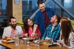 Друзья обедая и выпивая вино на ресторане Стоковое Изображение