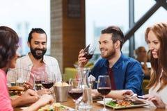 Друзья обедая и выпивая вино на ресторане Стоковое фото RF