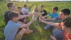 Друзья одноклассников clink стекла и едят мороженое outdoors в лете стоковые изображения rf