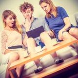 Друзья ослабляя интернет просматривать на таблетке Стоковые Изображения RF