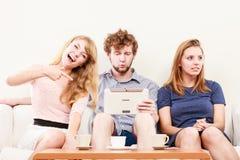 Друзья ослабляя интернет просматривать на таблетке Стоковое Фото