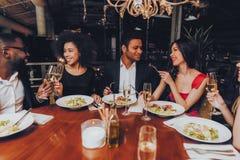Друзья охлаждая вне наслаждаться едой в ресторане стоковое фото rf