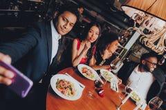 Друзья охлаждая вне наслаждаться едой в ресторане стоковое изображение rf