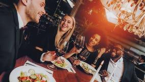 Друзья охлаждая вне наслаждаться едой в ресторане стоковые фото