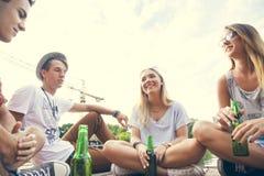 Друзья охлаждая около озера Стоковая Фотография