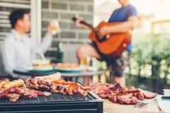 Друзья партийной группы после полудня наслаждаясь выпивающ пиво с гитарой свинины барбекю и жаркого счастливой играя наслаждаясь  стоковое изображение
