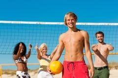 друзья пляжа играя волейбол Стоковые Фото