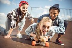 Друзья помогая стильному скейтборду катания девушки битника Стоковое Изображение RF