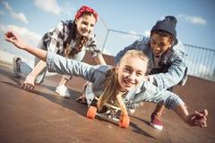 Друзья помогая стильному скейтборду катания девушки битника Стоковая Фотография