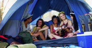 Друзья поя песню и играя гитару в шатре 4k сток-видео