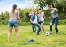 Друзья подростков бежать с шариком Стоковое Изображение RF