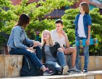 Друзья подростков говоря outdoors Стоковые Фотографии RF