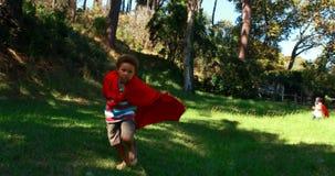 Друзья претендуя быть супергероем в парке акции видеоматериалы