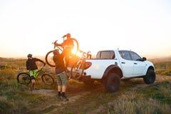 Друзья принимая велосипеды MTB с тележки приемистости Offroad в горах на заходе солнца Концепция приключения и перемещения стоковые фотографии rf