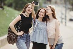 Друзья принимая selfie outdoors используя ретро камеру Стоковые Фотографии RF