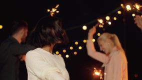 Друзья при бенгальские огни танцуя на партии крыши видеоматериал