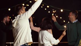 Друзья при бенгальские огни танцуя на партии крыши сток-видео