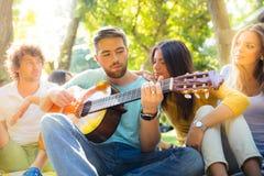Друзья при гитара имея потеху Стоковые Фото