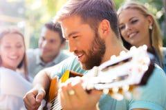 Друзья при гитара имея потеху Стоковое фото RF