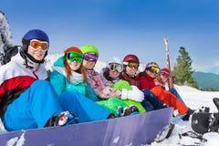 Друзья при сноуборды нося лыжу гуглят Стоковая Фотография