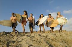 Друзья при Surfboards бежать на песчаном пляже стоковое фото
