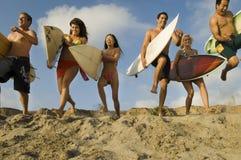 Друзья при Surfboards бежать на песчаном пляже Стоковое фото RF