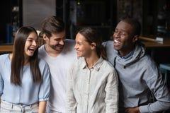 Друзья различной этничности тысячелетние имея потеху стоя внутри помещения стоковое фото