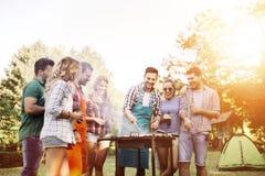 Друзья располагаясь лагерем и имея барбекю Стоковое Изображение RF